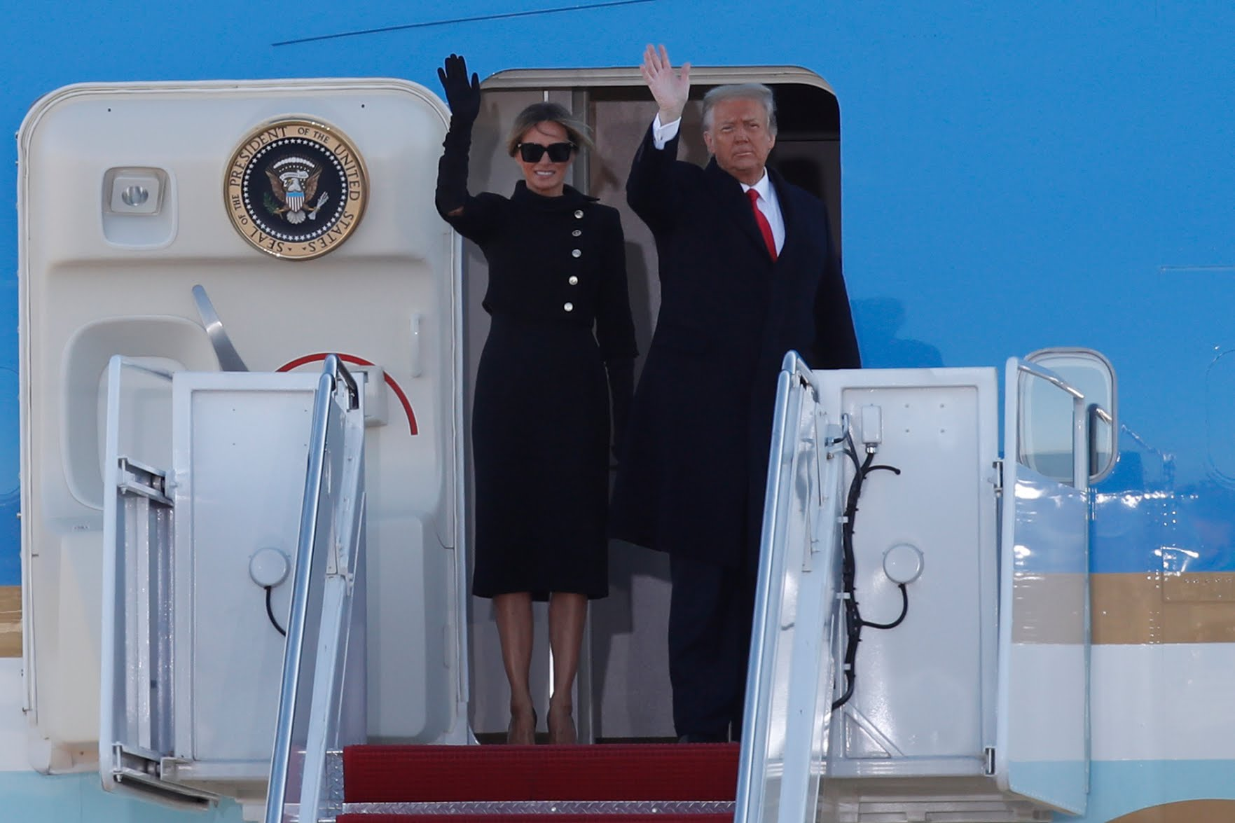 President Donald Trump and first lady Melania Trump wave to a crowd as they board Air Force One at Andrews Air Force Base, Maryland on Wednesday ahead of Joe Biden's inauguration. Breaking with long-standing tradition, Trump is not attending the inauguration. (Luis M. Alvarez/AP)