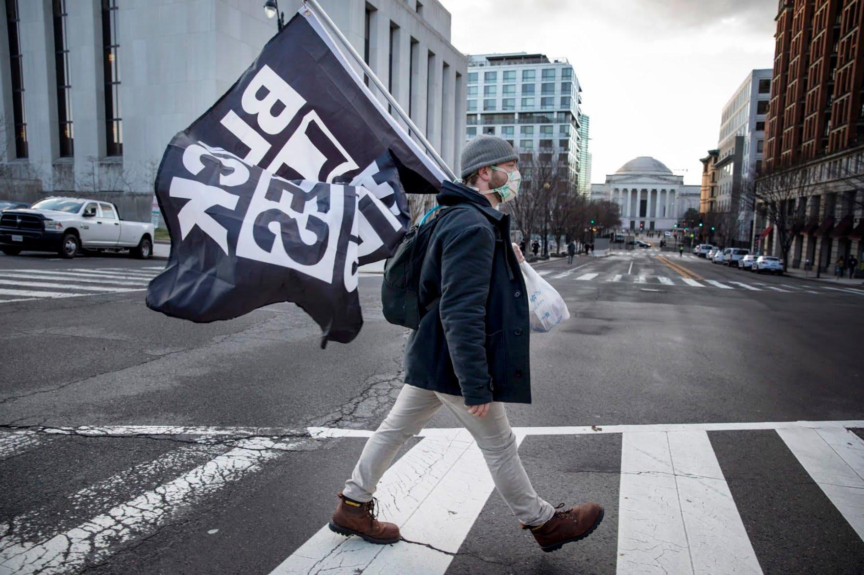 Jack Curtz, who lives in Boston, walks through downtown D.C. holding a Black Lives Matter flag. (Tyrone Turner/WAMU)
